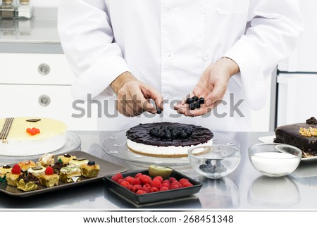 Chef preparing blueberry cake in kitchen - stock photo