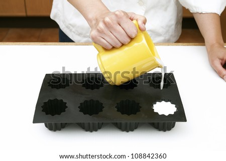 chef preparing desserts, filling molds with milk - stock photo