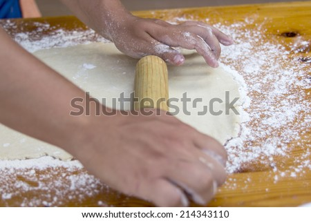 Chef preparing dough and ingredients of pizza at the kitchen