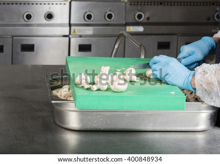 chef preparing food and cutting mushrooms in a restaurant kitchen - stock photo