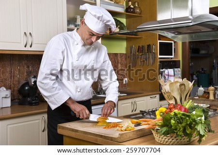 Chef preparing food in a kitchen - stock photo