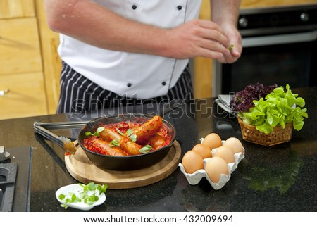 Chef preparing fried sausage in a frying pan with tomatoes sauce and egg.