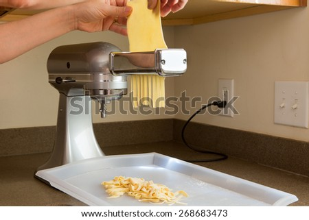Chef preparing homemade fettuccine pasta feeding the rolled sheets of dough through the cutting machine in the corner of a kitchen, close up view of the dough and appliance