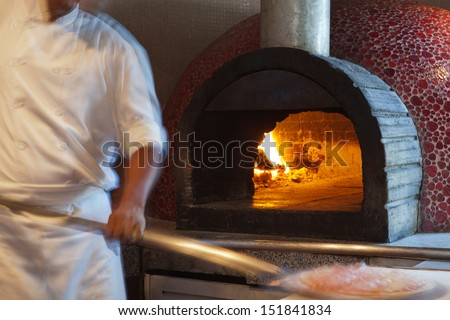 Chef preparing pizza in a wood oven - stock photo