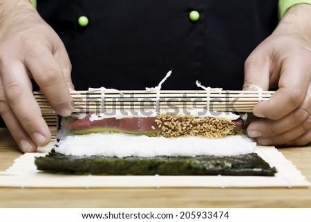 chef preparing sushi with rice, tuna, salmon and avocado - focus on the sesame - stock photo