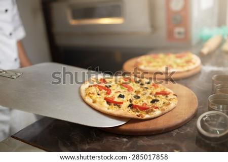 chef puts on the board freshly prepared pizza - stock photo