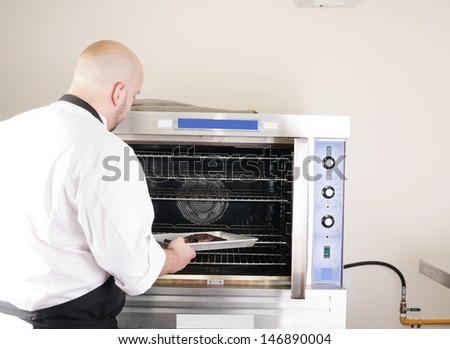 chef putting a tray of a juicy steak in a professional oven - stock photo