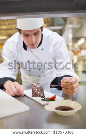 Chef putting berry coulis on the dessert in the kitchen - stock photo