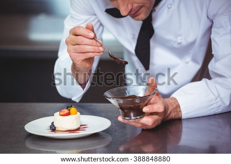 Chef putting chocolate sauce on a dessert in a commercial kitchen - stock photo