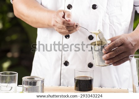 Chef putting condensed milk in to Hot coffee - stock photo