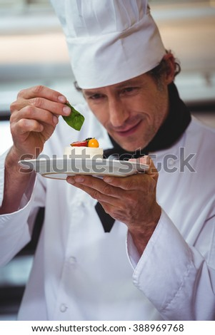 Chef putting finishing touch on dessert in commercial kitchen - stock photo