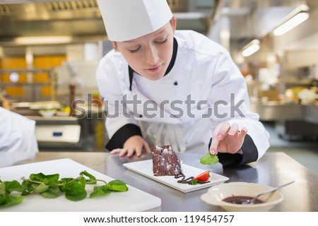 Chef putting mint with her chocolate cake in the kitchen
