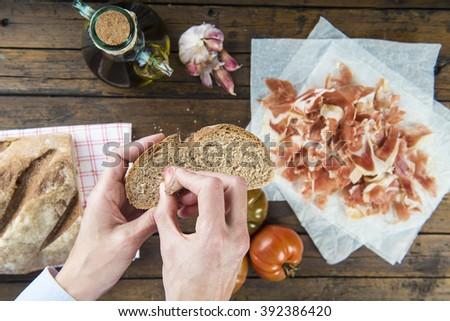 Chef rubbing garlic on a bread slice to prepare ham with garlic, tomato bread and olive oil Spanish style - stock photo