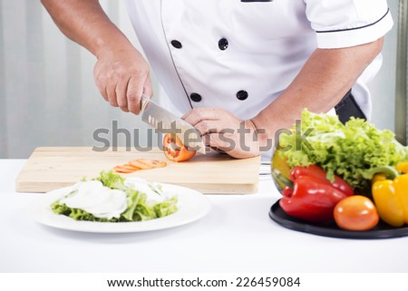 Chef's hands cutting Tomato,Making Salad Concept