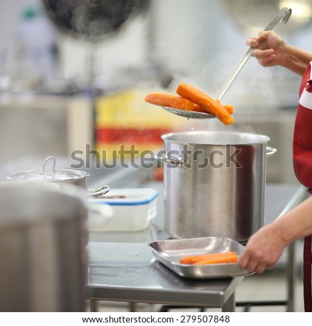 Chef's hands working in a kitchen; putting out some boiled carrots - stock photo