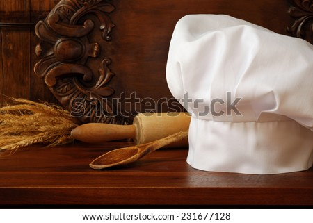 Chef's hat in rustic setting with vintage wooden spoon and rolling pin on wood cutting board..  Decorative, carved serving tray as background.  Baking or Cooking concept. - stock photo