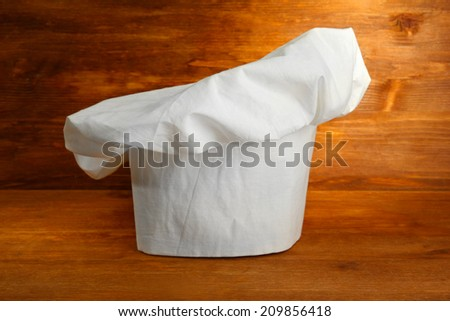 Chef's hat on wooden background - stock photo