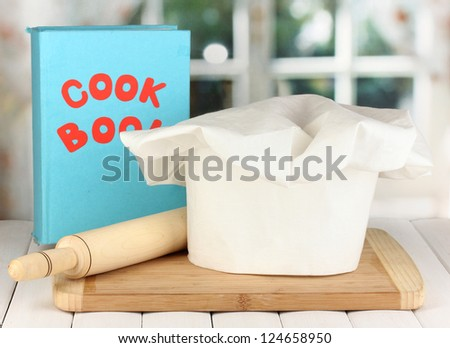 Chef's hat with battledore on board on wooden table on window background - stock photo