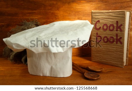 Chef's hat with spoons and cookbook on wooden background - stock photo