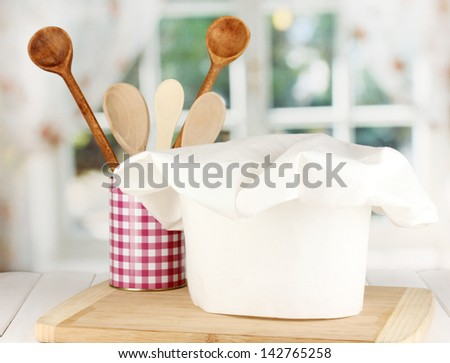 Chef's hat with spoons on board on wooden table on window background - stock photo