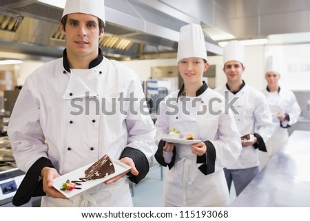 Chef's presenting deserts in the kitchen - stock photo