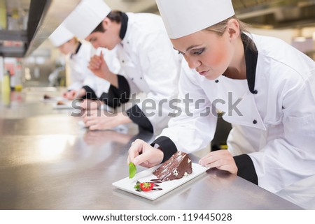 Chef's team garnishing slices of cake in the kitchen - stock photo