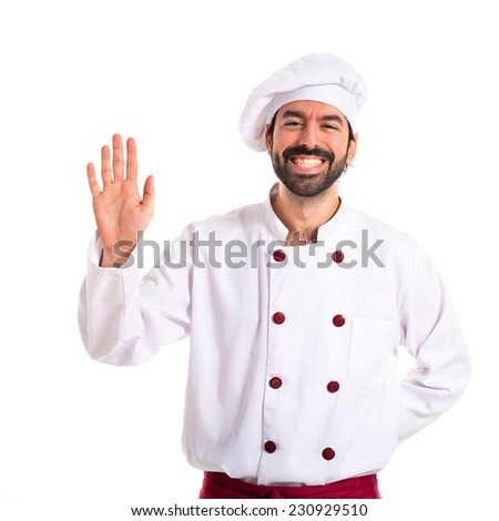 Chef saluting over white background - stock photo