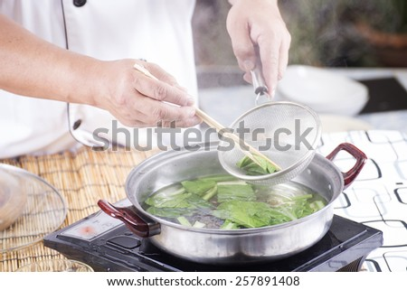Chef scald vegetable in pot before cooking noodle / Cooking Noodle concept