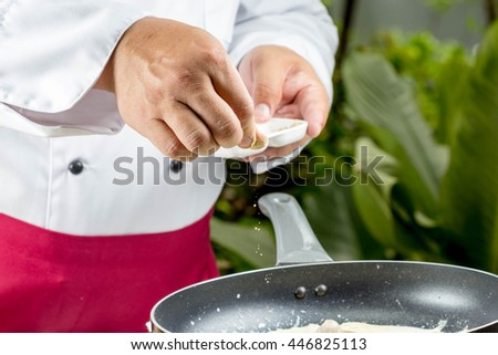 chef seasoning spaghatti to the pan