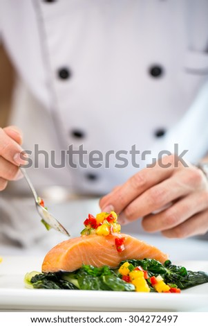 Chef setting delicious Fresh Samol with mango salsa in restaurant