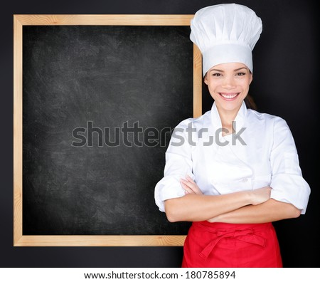 Chef showing menu blackboard. Woman in front of blank menu blackboard. Happy female chef, cook or baker by empty chalkboard menu display wearing chef whites uniform and hat - stock photo