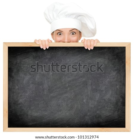Chef showing restaurant menu blackboard - empty blank copy space for text. Funny woman cook peeking over sign. Beautiful happy mixed race Caucasian / Asian female model. Isolated on white background. - stock photo
