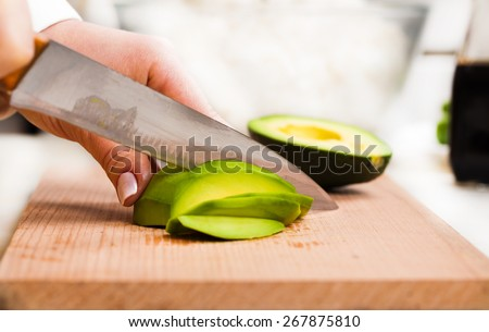 chef slicing the avocado close-up on a wooden board - stock photo