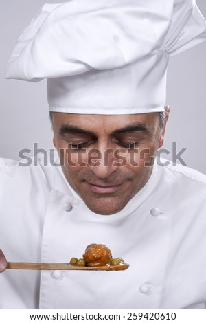 Chef smelling a spoonful of food - stock photo