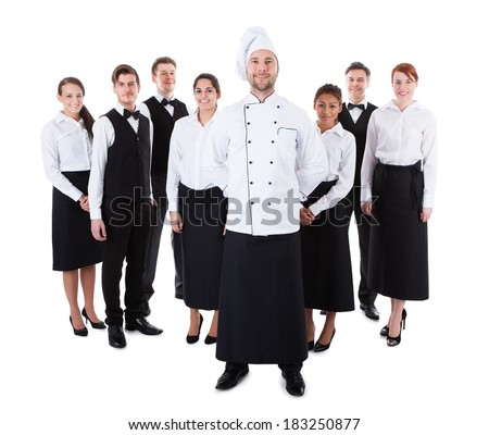 Chef standing in front of his team. Isolated on white