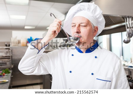 Chef tasting food in his kitchen - stock photo