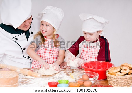 Chef teaches children to knead the dough - stock photo