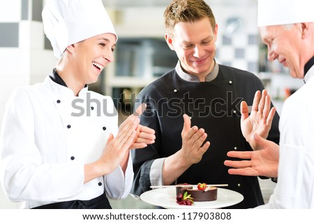 Chef team in restaurant kitchen with dessert, the colleagues applauding because the dish works great - stock photo