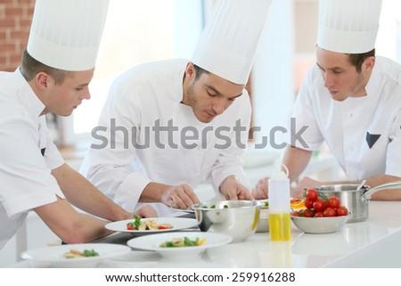 Chef training students in restaurant kitchen - stock photo