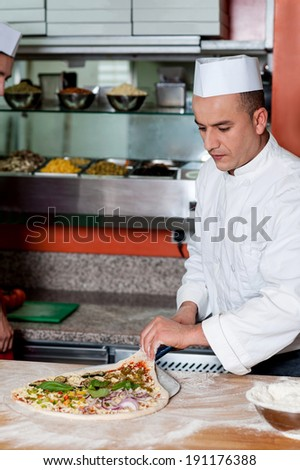 Chef trying to take out the pizza dough