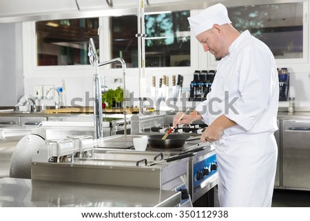 Chef using brush to prepare a dish in the kitchen - stock photo