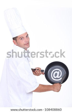 Chef with an sign on his frying pan - stock photo
