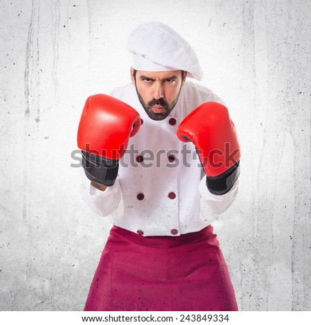 Chef with boxing gloves over textured background - stock photo