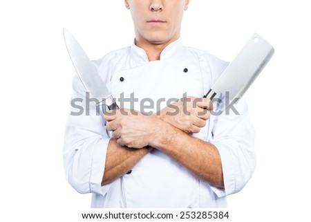 Chef with knifes. Close-up of confident mature chef in white uniform holding knifes in his hands while standing against white background - stock photo