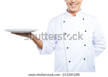 Chef with plate. Close-up of confident mature chef in white uniform holding empty plate and smiling while standing against white background - stock photo