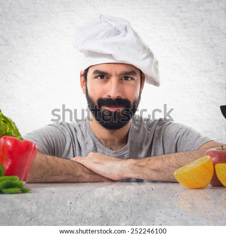 Chef with several vegetables and fruits on table - stock photo