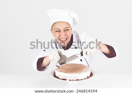 Chef with white hat preparing delicious chocolate cream cake while smiling - stock photo