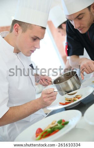 Chef with young cook in kitchen preparing dish - stock photo