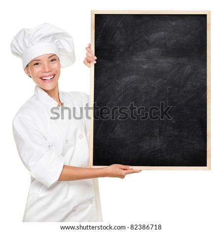 Chef. Woman cook showing empty menu chalkboard with copy space. Happy smiling Asian Caucasian female chef isolated on white background holding nice textured blackboard for advertising. - stock photo