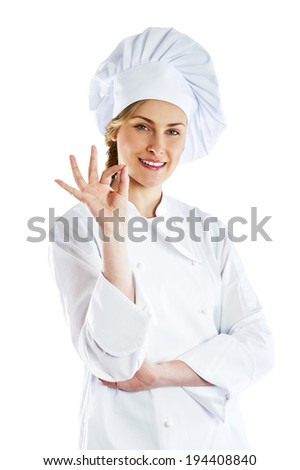 Chef woman giving a Perfect gesture with hand. Young beautiful female chef with a beaming smile standing in a toque chefs hat and whites and apron giving a Perfect gesture with her fingers - stock photo